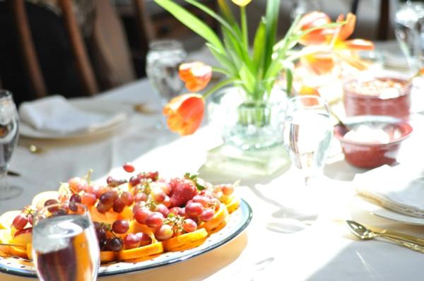 Antipasti semplici e veloci, fettine di pesca con uva, tavolo apparecchiato, vaso con tulipani