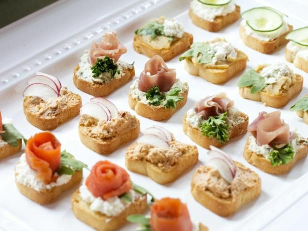Brunch con bruschette, fette di pane con salmone, crema spalmabile per panini