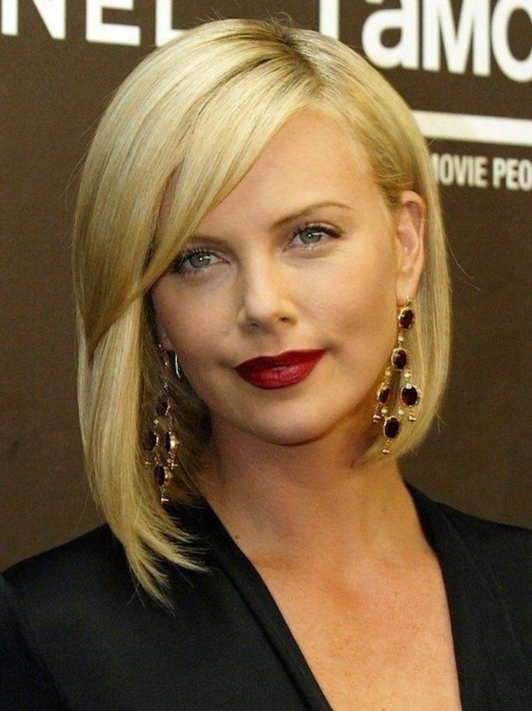 Donna con frangia, capelli di colore biondo, rossetto rosso dark, taglio corto scalato, donna con occhi azzurri