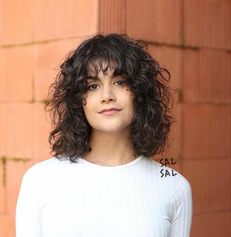Taglio corto asimmetrico, capelli colore nero con frangia, donna con capelli ricci