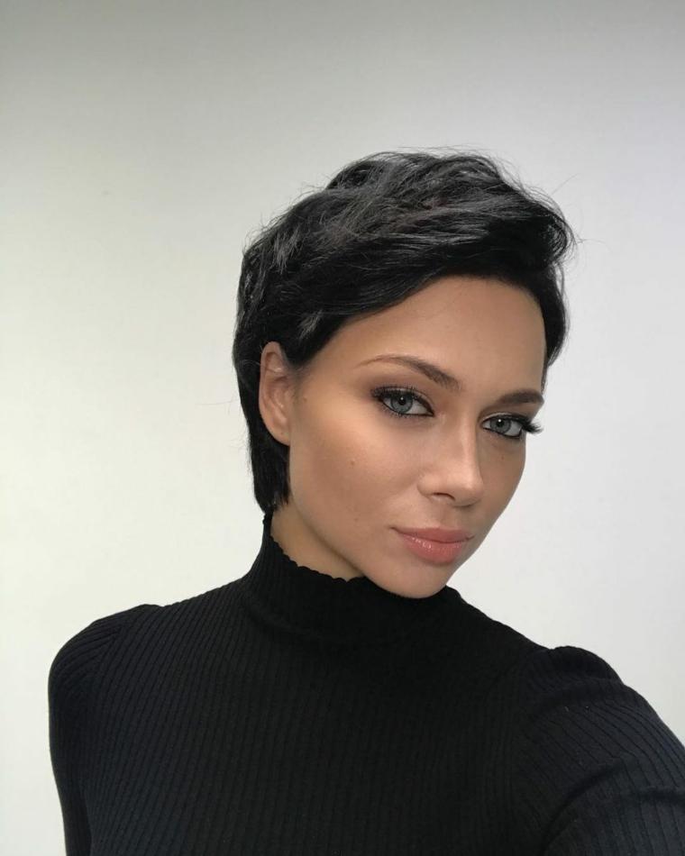Caschetto corto, donna con capelli neri, pettinatura effetto mosso, maglione collo alto nero