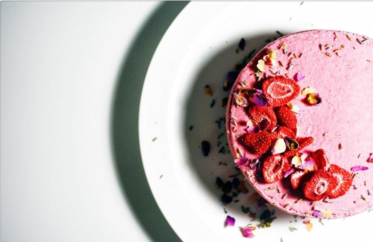 Torta rotonda con fragole, decorazione torta con fragole, piatto con foglie viola