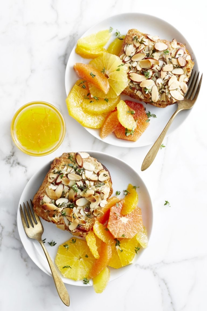 Colazione con panino, toast con mandorle, fettine di arancia, bicchiere succo di arancia