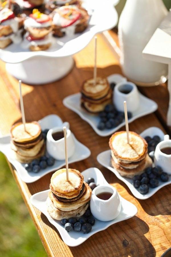 Colazione con mini pancakes, spiedini di pancake e mirtilli, bicchiere con sciroppo d'acero