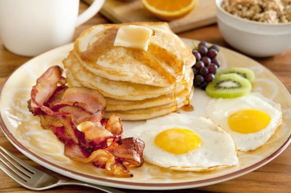 Piatto con pancake e becon, uovo all'occhio di bue, fettine di wiki e chicchi di uva