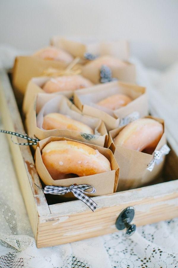 Sacchettini di carta con ciambelle, cestino di legno con dolci, colazione e brunch