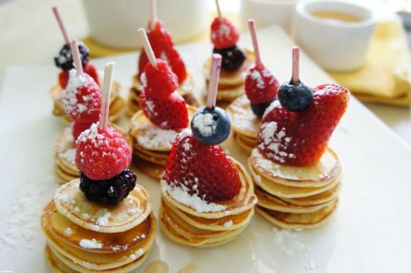 Spiedini di frutta, mini pancake con zucchero a velo, spiedini con more e lamponi