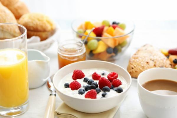 Colazione con yogurt e frutti di bosco, bicchiere con succo, barattolo con marmellata
