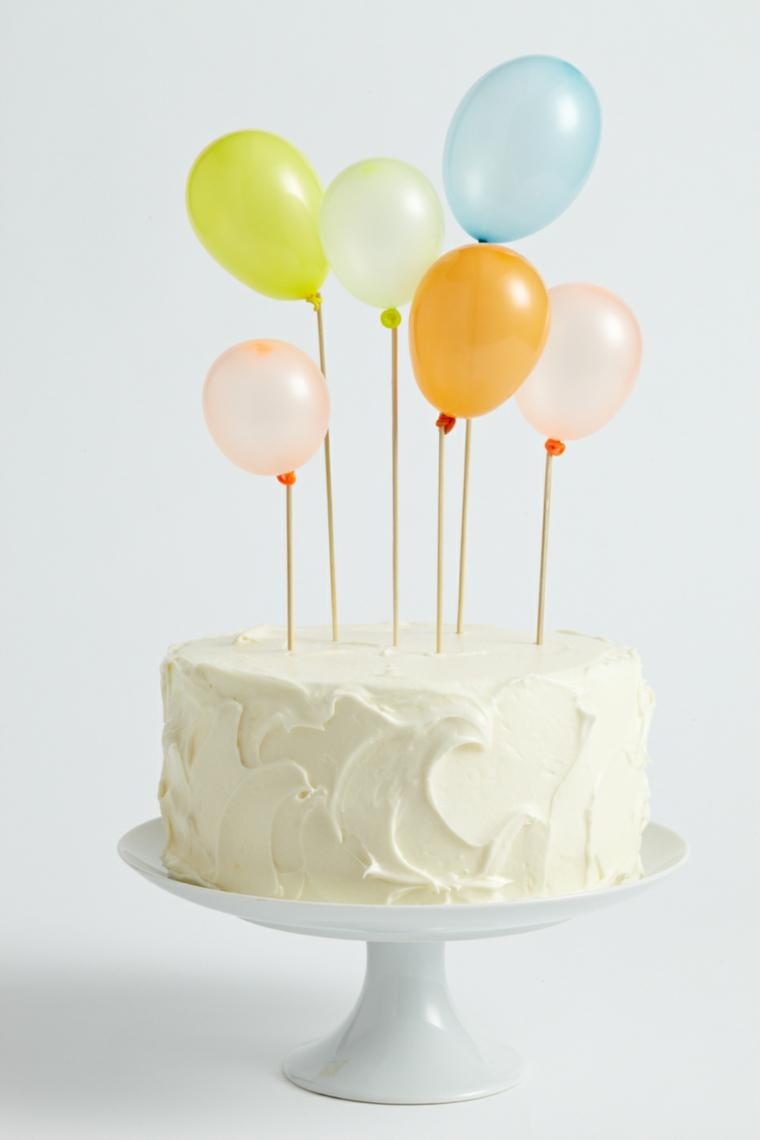 Torta con cioccolato bianco, topper con palloncini, torta dalla forma rotonda