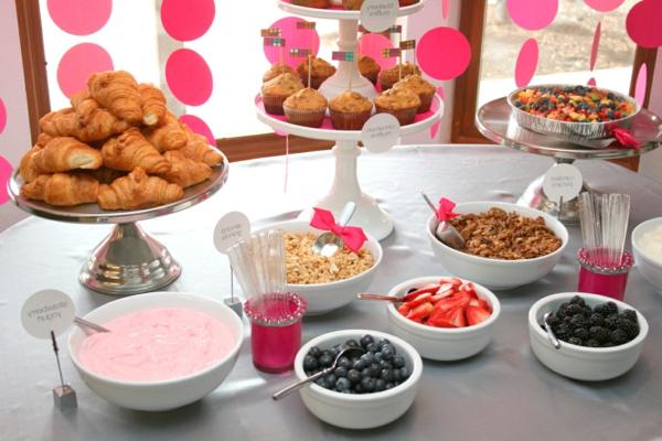 Buffet con la colazione, brioche e muffin, ciotole con frutti di bosco, cucchiai con fiocchi rosa
