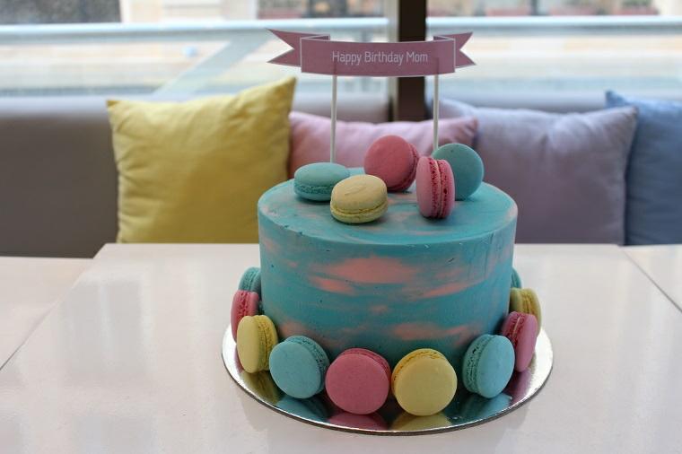 Torta con crema pasticcera blu, topper con ghirlanda, decorazione torta con macaron