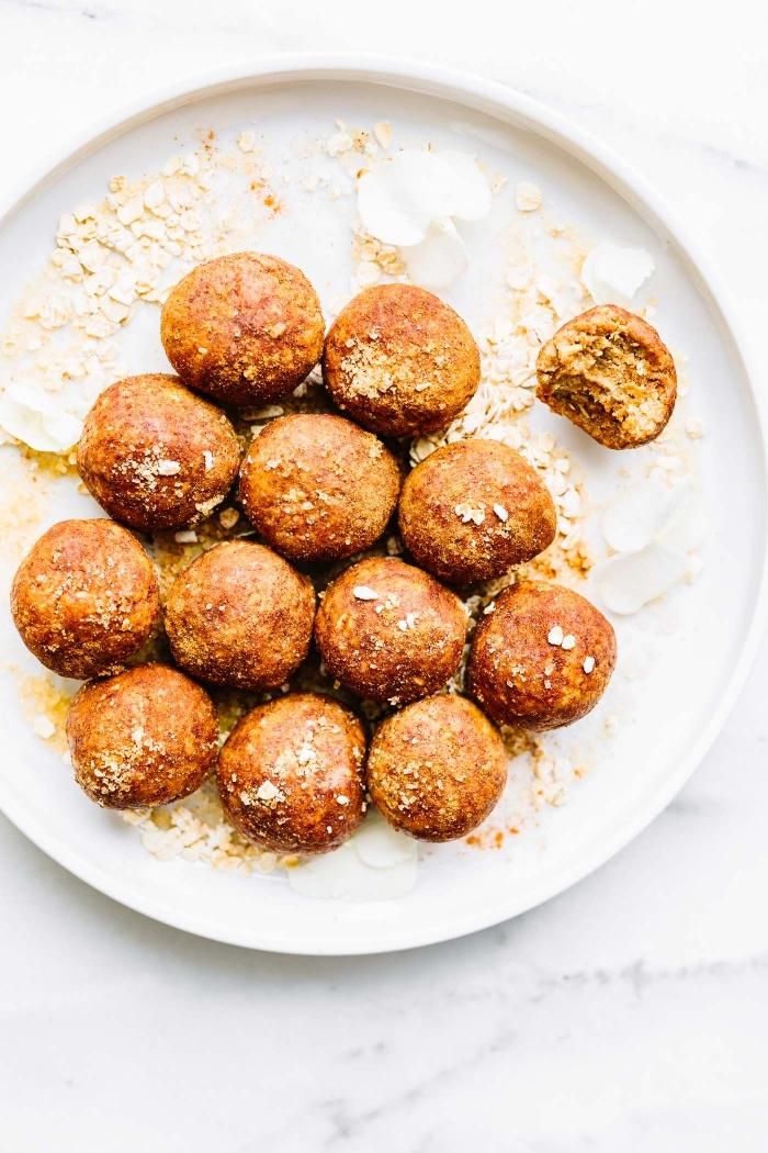 Palline dolci fritte, piatto bianco e tondo, decorazione piatto con zucchero a velo
