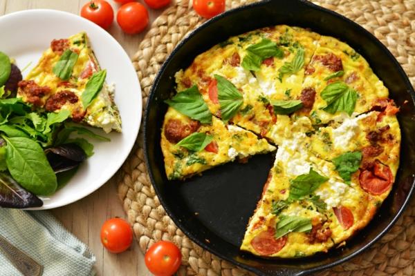 Frittata con uova e salame, foglie di basilico, brunch con insalata e uova