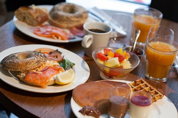 Antipasti freddi per buffet, panino con sesamo, ciotola con frutta, bicchiere con succo di frutta