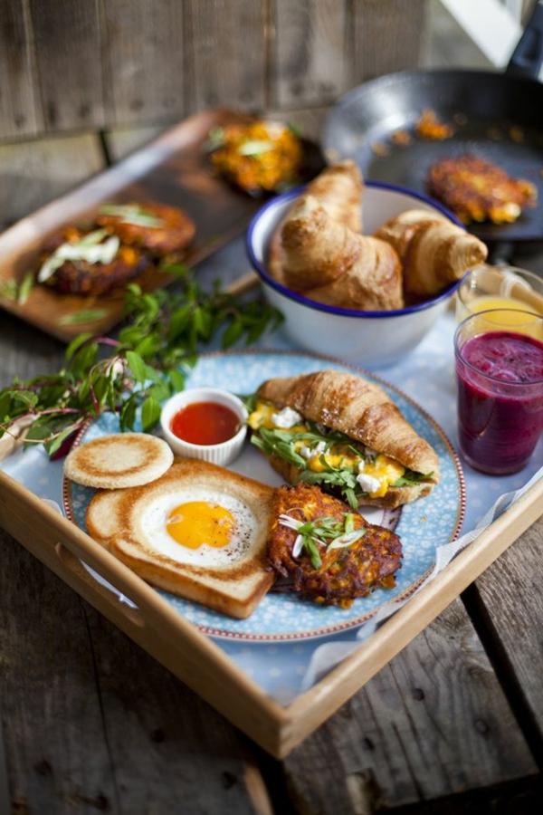 Cibi da brunch, vassoio di legno, panino salato con guacamole, uova al tegamino in una fetta di pane