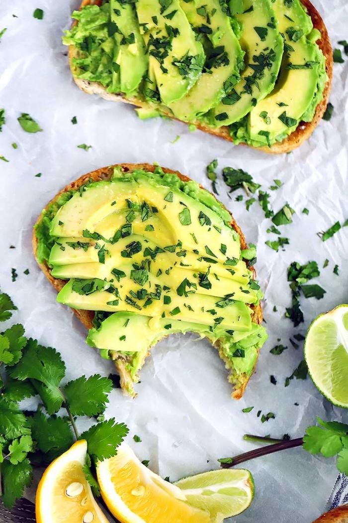 Antipasti freddi per buffet, fetta di pane con avocado, fette di avocado cosparse con prezzemolo