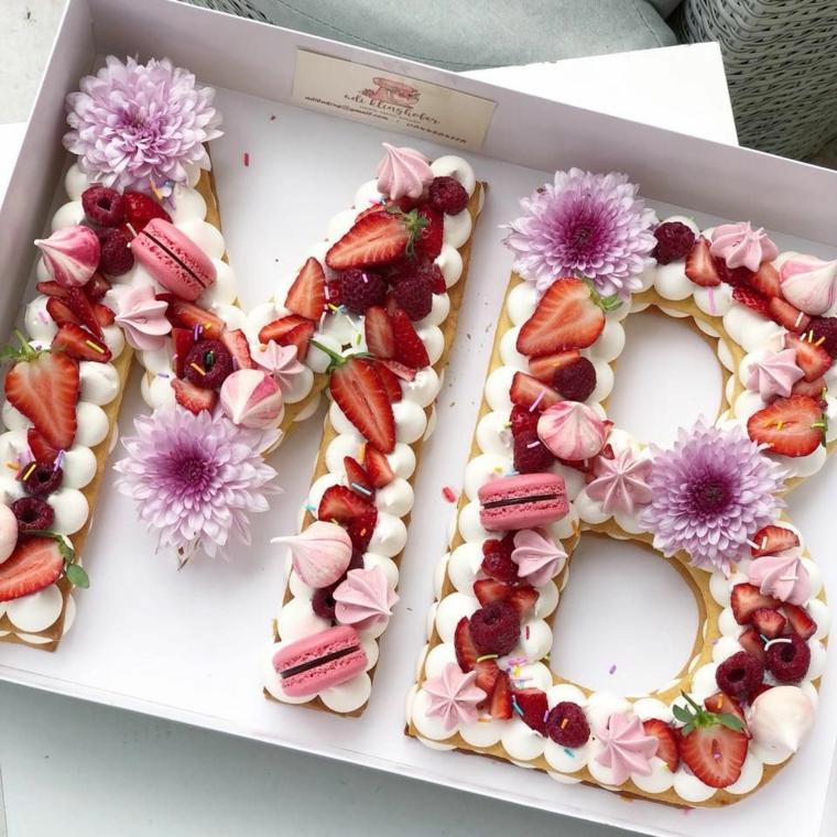 Scatola con torta, torta con lettere di biscotto, decorazione con fragole e macaron