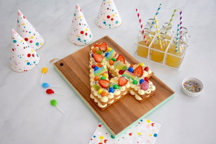 Torta bimbo 4 anni, decorazione con fragole, cappellini colorati, bottiglie con cannucce e succo
