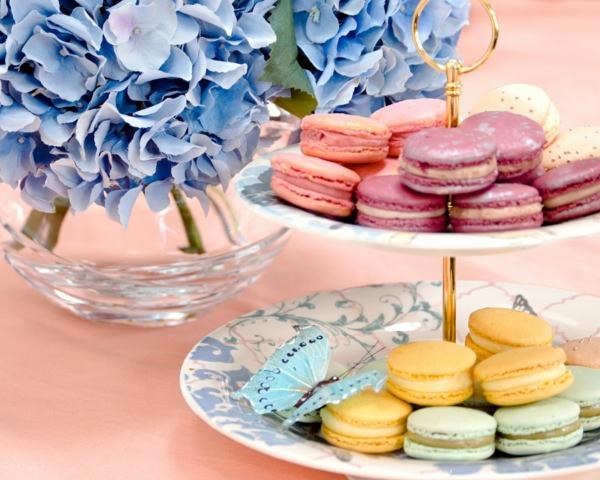Macarons colorati, colazione con dolci, vaso di fiori, petali di colore blu