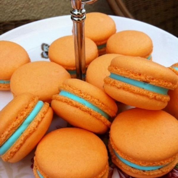 Macarons di colore arancione, ripieno dolcetti crema azzurra, colazione con dolci