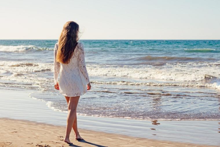 Matrimonio in spiaggia, donna con vestito pizzo ricamato, spiaggia con sabbia