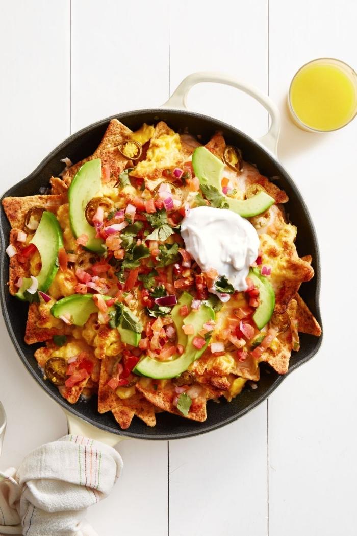 Tegame con nachos, fette di avocado, brunch significato, bicchiere con succo di arancia