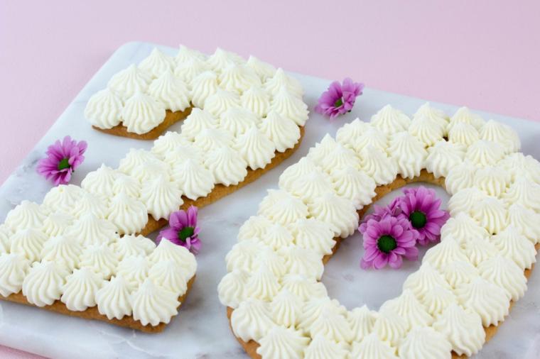 Torta con biscotto, decorazione con panna montata, fiorellini con foglie viola