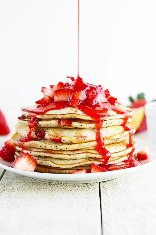 Colazione con pancakes, marmellata di fragole, pezzettini di fragole, tavolo di legno