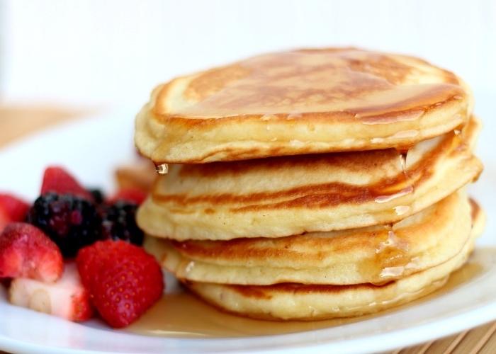 Colazione con pancakes, fragole tagliate a fette, pancakes per il brunch