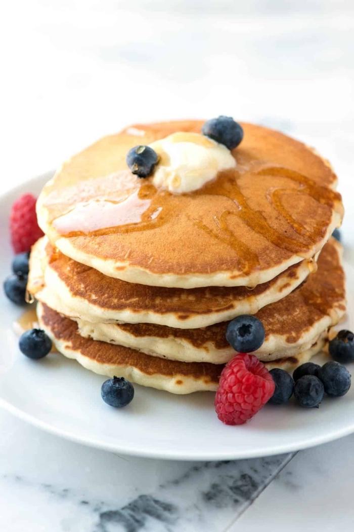 Colazione con pancakes, sciroppo d'acero, frutti di bosco, lamponi e mirtilli