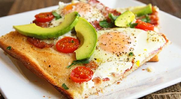 Piatti freddi estivi, pizza con avocado, pezzettini di pomodorini, uovo in camicia