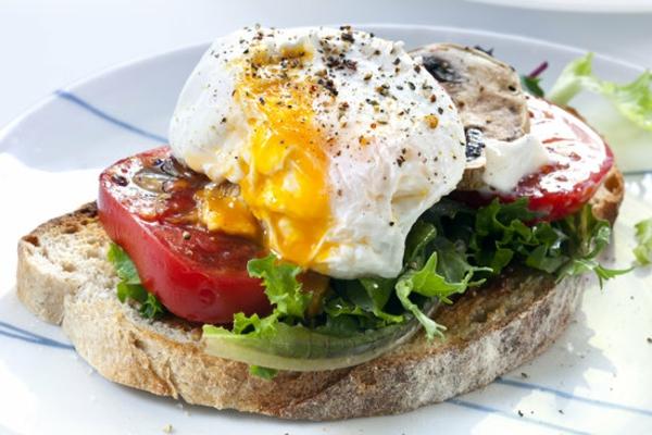 Fetta di pane con insalata e pomodori, uovo in camicia con pepe nero, brunch con toast