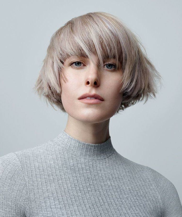 Taglio capelli corti donna, capelli di colore biondo ash, acconciatura con frangia, maglione grigio donna