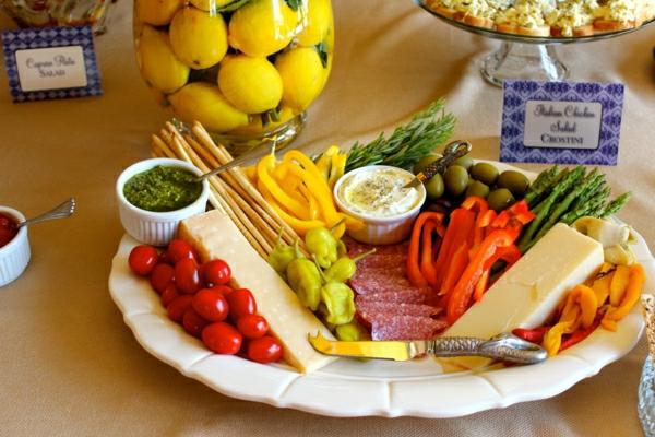 Piatto con verdure e formaggio, pomodorini ciliegio, vaso con limoni, ricette antipasti sfiziosi