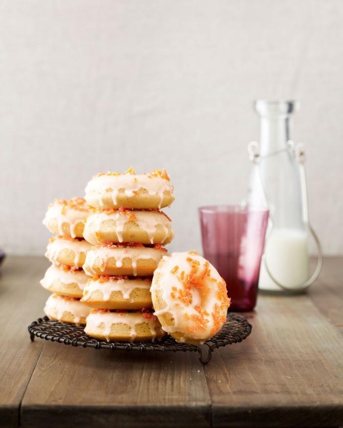Ciambelle con glassa bianca, ciambelle con codette di zucchero, tavolo di legno