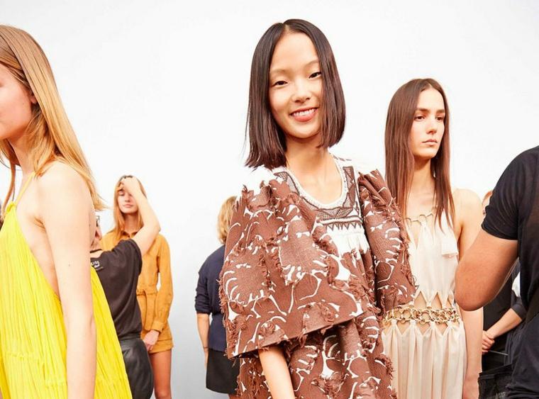 Taglio corto dietro e lungo davanti, capello bob colore castano, ragazze ad una sfilata di moda
