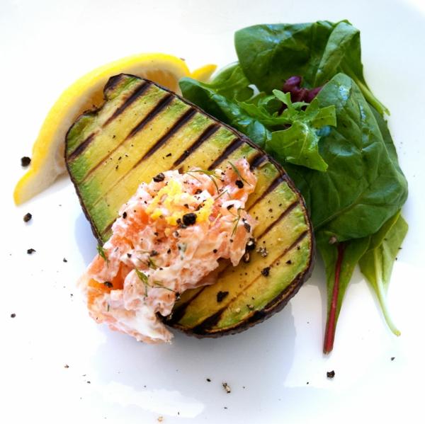 Idee brunch, avocado grigliato con spinaci, una fetta di limone, salmone con maionese