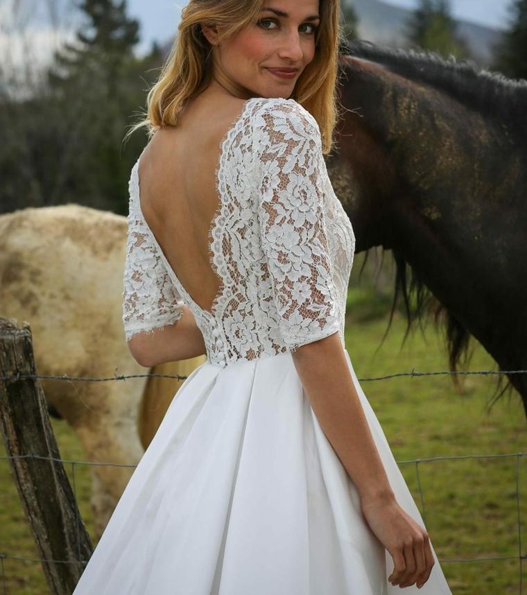 Donna e un cavallo, bustino abito in pizzo bianco, abito corto da sposa, vestito con schiena scoperta