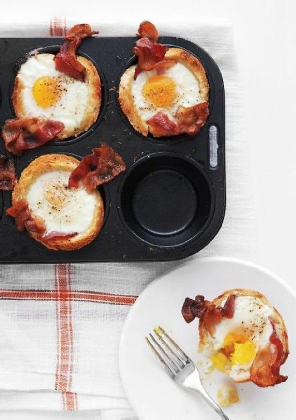 Cibi da brunch, muffin con becon e uova, uovo in camicia, piatto e forchetta