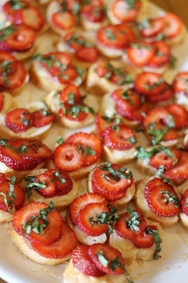 Fette di baguette con fragole, pezzettini di fragola, decorazione con erbette fresche