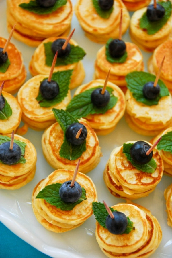 Colazione con mini pancake, spiedini con mirtilli, foglie di menta di colore verde