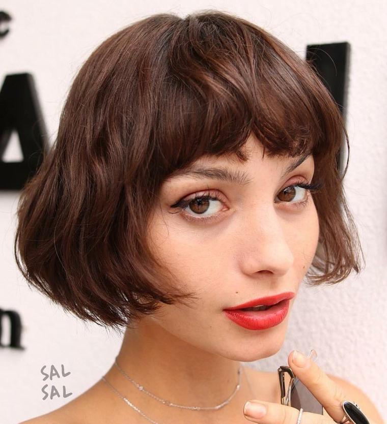 Caschetto corto, donna con capelli castani, acconciatura con frangia, trucco con rossetto rosso