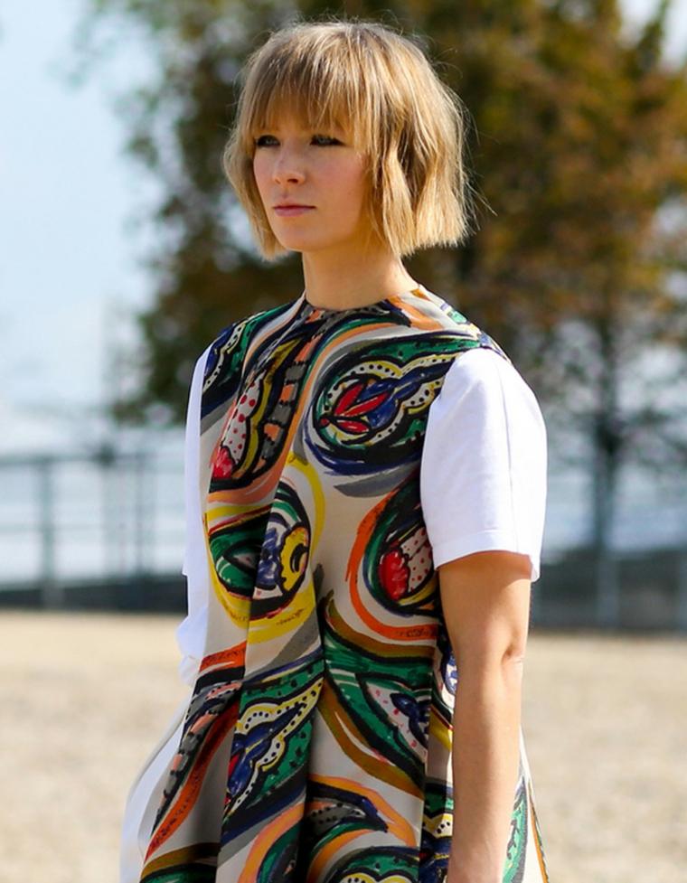 Donna con abito colorato, capelli di colore biondo, acconciatura capelli con frangia