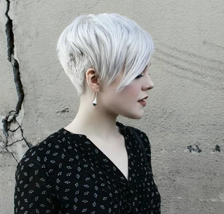 Donna con capelli biondi, taglio asimmetrico cortissimo, pettinatura con frangia