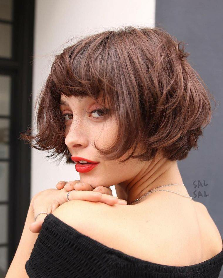 Donna con capelli di colore castano, acconciatura con frangia, rossetto rosso lucido