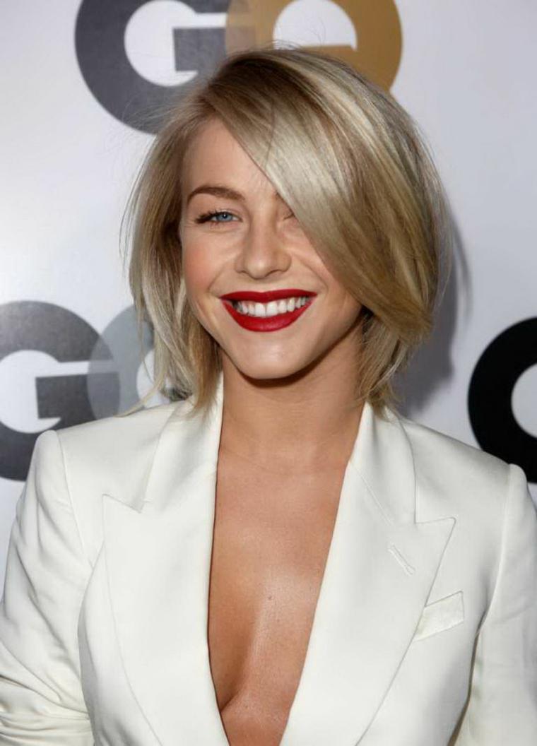 Donna con capelli scalati corti, colore capelli biondo, giacca bianca con scollo