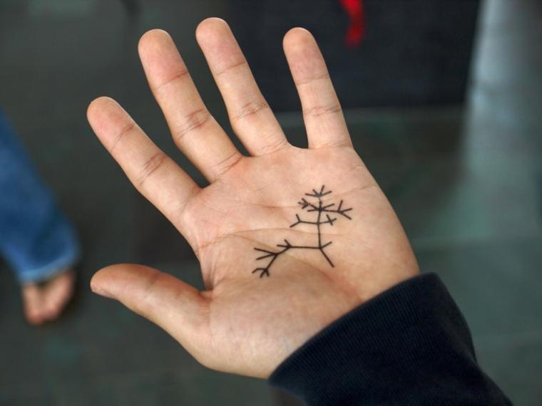 Tatuaggio sul palmo della mano, disegno tatuaggio rami, uomo con la mano tatuata