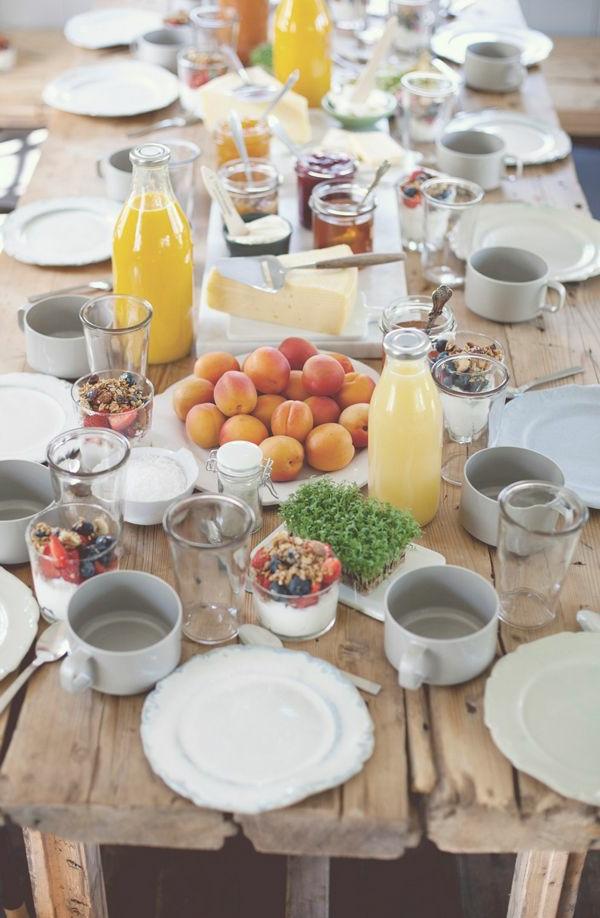 Tavolo di legno apparecchiato, brunch con frutta, bottiglie con succo, dolce al cucchiaio