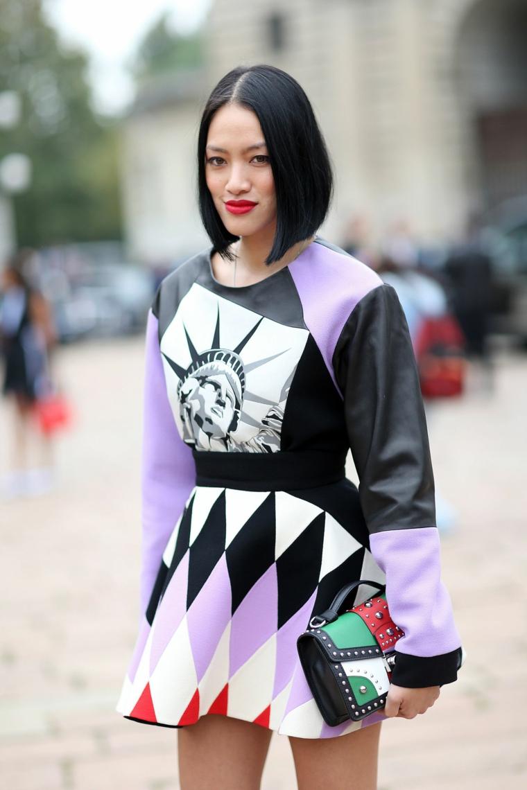 Taglio corto femminile, donna con capelli neri, pettinatura con riga centrale, abito con motivi geometrici