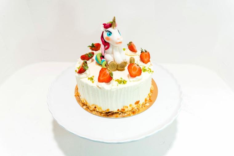 Torta con panna montata, decorazioni con topper unicorno, decorazione con fragole
